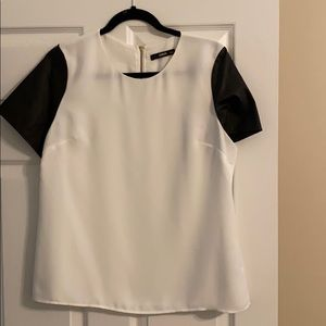 White top with black faux leather sleeves